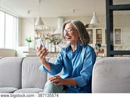 Happy Mature Old 60s Woman Holding Smartphone Using Mobile Phone App For Video Call, Laughing While