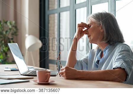 Tired Old Senior Business Woman Taking Off Glasses Suffers From Eyestrain, Stress, Headache, Fatigue