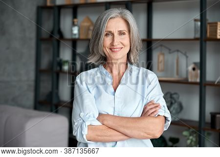 Smiling Confident Stylish Mature Middle Aged Woman Standing At Home Office. Old Senior Businesswoman