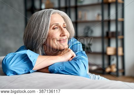 Happy Relaxed Mature Old Woman Resting Dreaming Sitting On Couch At Home. Smiling Mid Aged Woman Rel