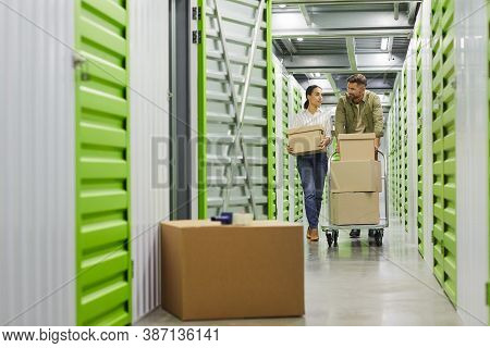 Full Length Portrait Of Young Couple Holding Cardboard Boxes Walking Towards Camera In Self Storage