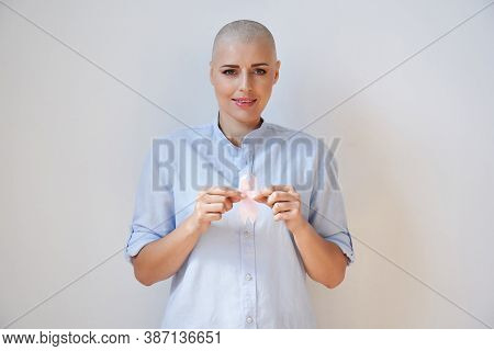 Happy Optimistic Bald Young Woman Breast Cancer Patient Survivor Holding Pink Ribbon Isolated On Whi