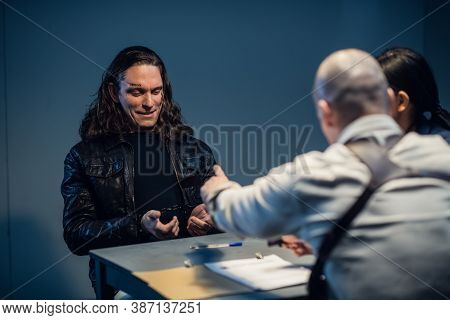 Interrogation Of A Homicidal Maniac In The Interrogation Room. A Police Detective Sits At A Table Wi
