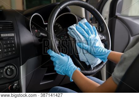 Hand Wearing Rubber Gloves Cleaning Car Steering Wheel With Microfiber Cloth, Clean The Car Interior