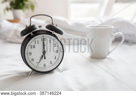 Alarm clock morning wake-up time on bed with coffee cup