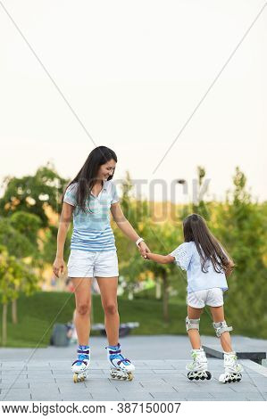 Smiling Mother And Little Daughter Rollerskating In Summer Park. Family Concept
