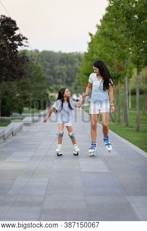 Happy Mother And Her Little Daughter Rollerskating In Summer Park. Family Have Fun