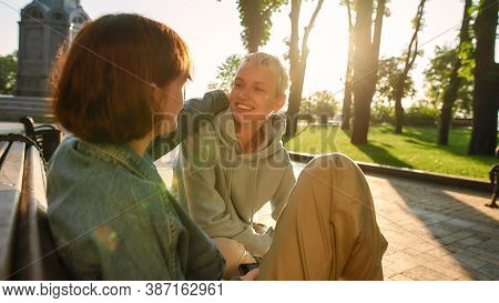 Two Young Women Having Fun, Talking While Sitting On The Bench In The City Park. Lesbian Couple Spen