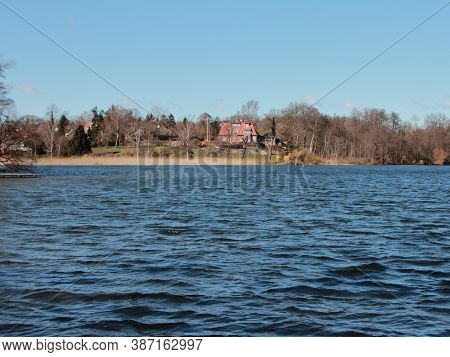 A Large Red House By A Silent Blue Lake. Trees Surround The House.