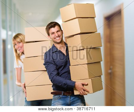 Man And Woman Holding Stack Of Cardboard, Indoor