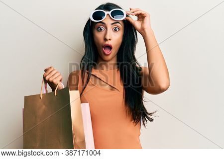 Beautiful hispanic woman holding shopping bags wearing sunglasses afraid and shocked with surprise and amazed expression, fear and excited face.