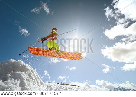 Woman Skier Athlete Makes A Jump In Flight On A Snowy Slope Against The Backdrop Of A Blue Sky Of Mo