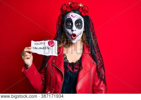 Woman wearing day of the dead costume holding happy halloween paper scared and amazed with open mouth for surprise, disbelief face