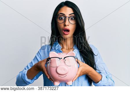Beautiful hispanic woman holding piggy bank with glasses afraid and shocked with surprise and amazed expression, fear and excited face.