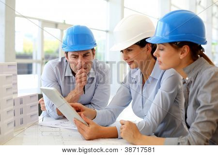Architects working in office on construction project