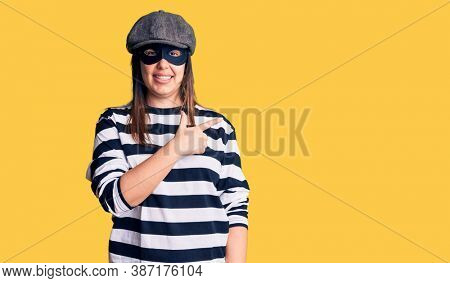 Young beautiful brunette woman wearing burglar mask cheerful with a smile of face pointing with hand and finger up to the side with happy and natural expression on face