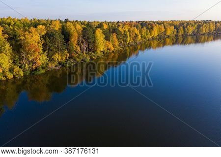 Aerial Photo Of A Surface Of The Lake Surrounded By Colorful Forest In Autumn.