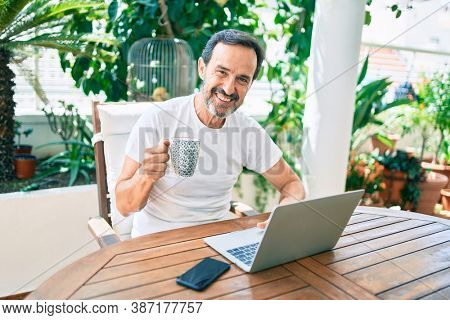Middle age man with beard smiling happy at the terrace working from home using laptop drinking a cup of coffee