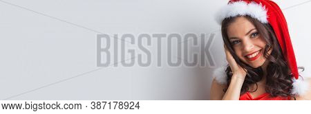 Happy christmas santa woman smiling. Beautiful face of happy caucasian woman posing in santa hat, white background with copy space