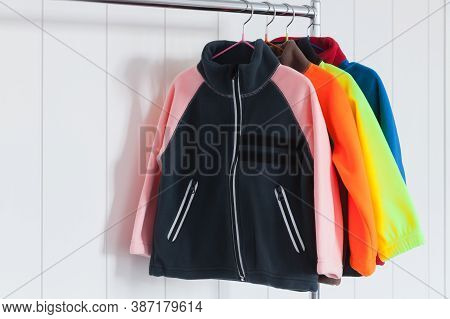 Colorful Fleece Jackets Are Hanging On Hangers Near White Wall