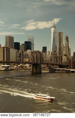 Brooklyn Bridge and downtown Manhattan skyline with boat in New York City