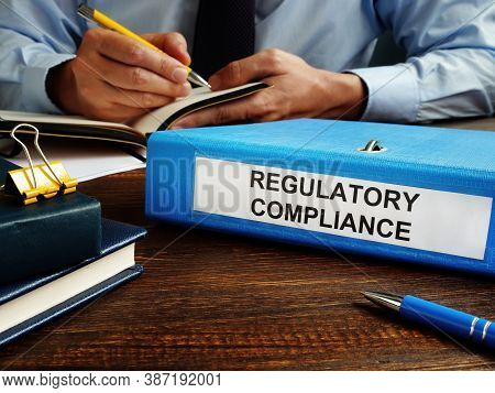 Regulatory Compliance Papers In The Folder And Manager.