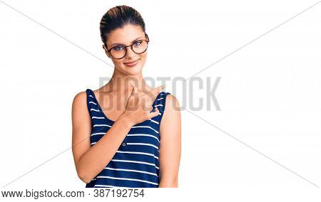 Young beautiful woman wearing casual clothes and glasses cheerful with a smile of face pointing with hand and finger up to the side with happy and natural expression on face