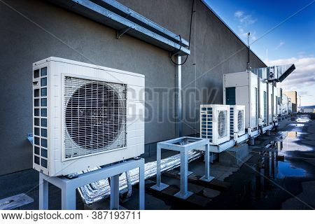 Square Air-conditioning Unit On The Roof With A Round Fan. In The Background Gradually Receding Othe