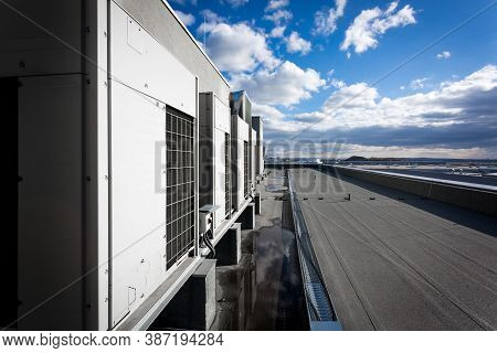 A Series Of Gradually Receding Air Conditioning Units On The Roof With Blue Sky And Clouds In The Ba