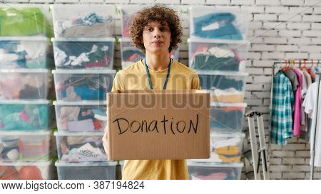 Caucasian Guy Holding Donation Box And Looking At Camera, Posing In Front Of Rack And Boxes Full Of