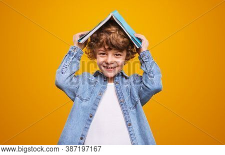Cheerful Child In Denim Jacket Smiling For Camera And Covering Head With Book During Lesson Against