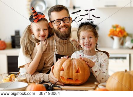 Happy Family   Father  And Children Daughters Prepare For Halloween By Carving Pumpkins At Home In T
