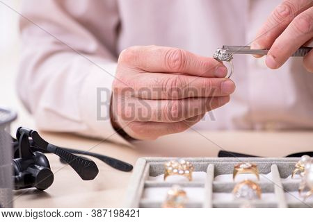 Old male jeweler at workshop