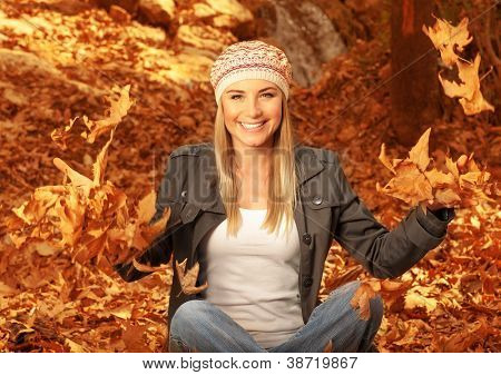 Picture of happy blonde girl having fun in autumn woods, pretty woman throwing up dry autumnal leaves in the forest, beautiful female sitting down on ground covered golden foliage