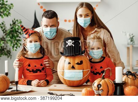 Cheerful Family  In Medical Masks Makes Jack O Lantern Out Of A Pumpkin And  Decorates House  In Coz