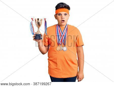 Little boy kid holding champion trophy and wearing medals scared and amazed with open mouth for surprise, disbelief face