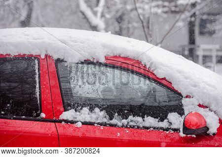 Closeup Photo Of Red Parked Car Cover With Snow After Blizzard