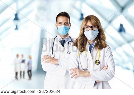 Shot Of Female And Male Doctors Wearing Face Masks While Standing Together At Hospital's Foyer. Medi
