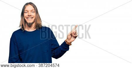 Handsome caucasian man with long hair wearing casual winter sweater with a big smile on face, pointing with hand finger to the side looking at the camera.