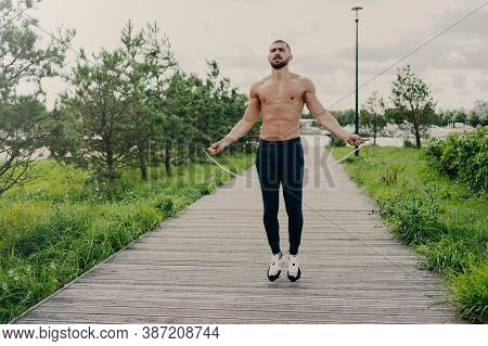 Sporty Muscular Man Uses Skipping Rope For Cardio Training Outdoor, Has Perfect Body, Breathes Fresh