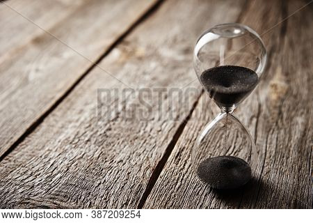 Hourglass On Wooden Background, Close Up. Urgency And Running Out Of Time Concept