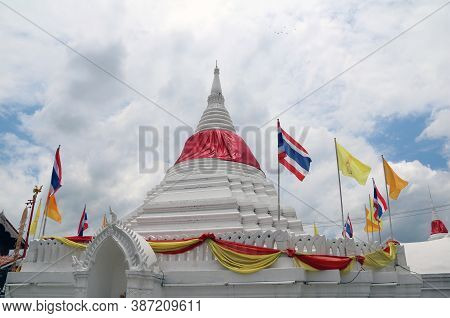 White Pagoda Has A Red Cloth Tied At The Top Surrounded By Thai National Flag, Yellow King Rama 9 Fl