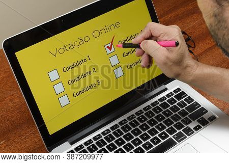 Person Voting On The Computer Over The Internet With The Text Online Voting In Portuguese