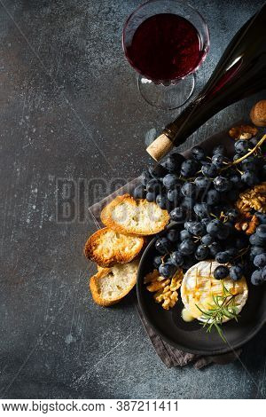 Roast Camembert And Honey With Black Grapes And Baked Slice Of Bread On Dark Background, Copy Space,