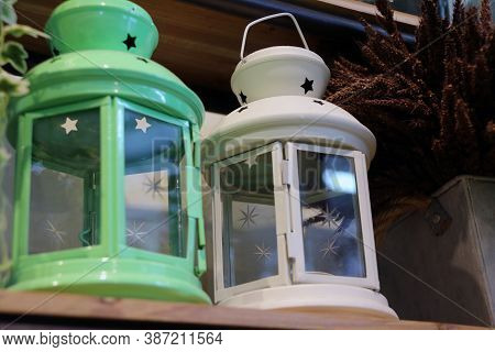 White Lantern And Green Lantern On The Wooden Step. Metal Lamp With Clear Glass.