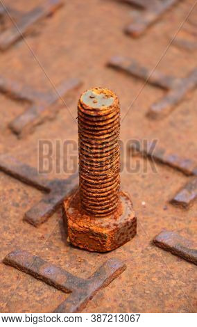 Rusty Metal Bolt Put Up On The Steel Plate Floor In Brown Color With Rusty Iron. Rust Is A Reddish O