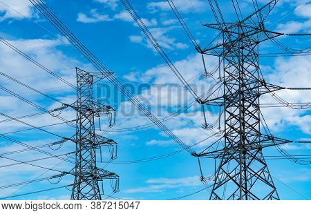High Voltage Electric Pylon And Electrical Wire Against Blue Sky And Clouds. Bottom View Of Electric