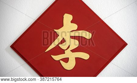 The Surname Sign On The White Wall, The Golden Chinese Word Handwriting Style On The Red Wooden Sign