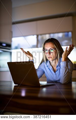 Pretty, middle-aged woman working late in the day on a laptop computer at home, running a business from home/working remotely - getting frustrated