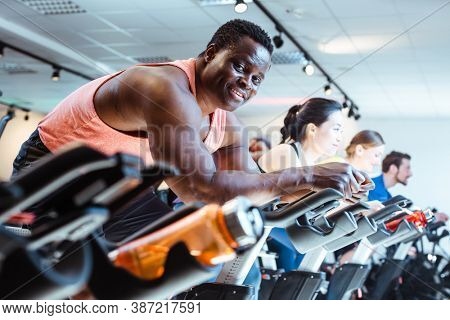 African man and friends exercising on fitness bike in gym